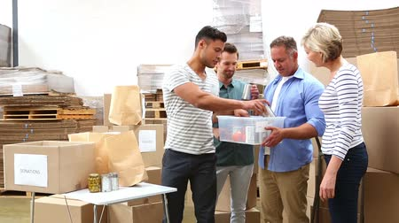 благотворительность : Warehouse workers packing up donation boxes in a large warehouse