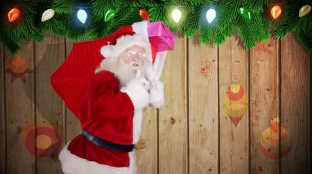 доставлять : Digital animation of Santa carrying sack of gifts against festive wooden background