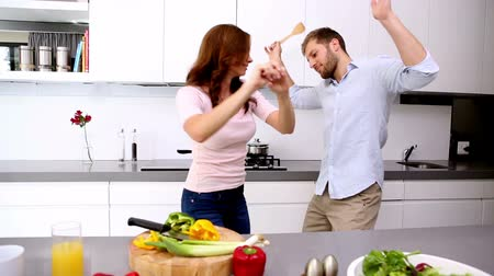 mutfak : Couple dancing and acting silly in the kitchen with vegetables on the counter Stok Video