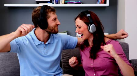 ostoba : Couple listening to music and acting silly at home on the couch