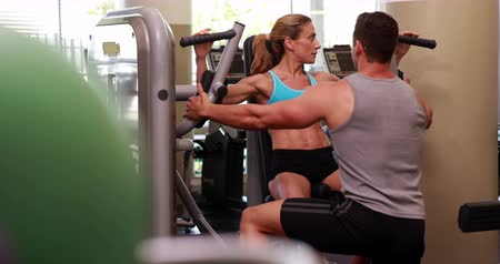 eğitici : Fit woman using weights machine for arms with her trainer at the gym