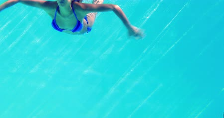 swimming underwater : Sexy blonde in blue bikini jumping into the swimming pool on a sunny day