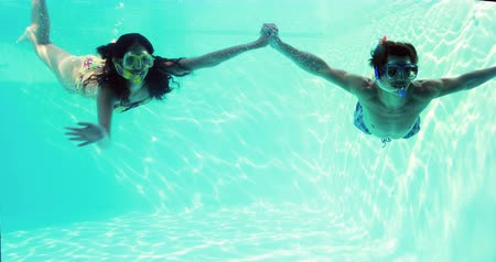 šnorchl : Happy couple jumping in swimming pool together wearing snorkels on their holidays Dostupné videozáznamy