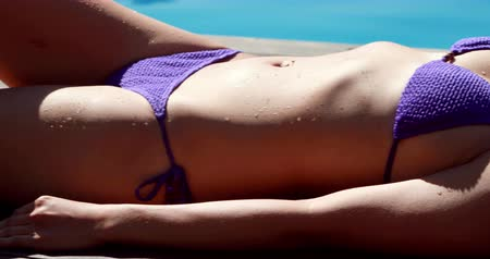 charming : Sexy brunette lying poolside sunbathing on a sunny day Stock Footage