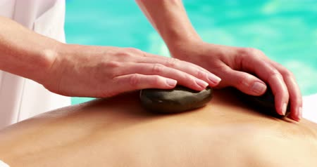 terapeuta : Beauty therapist rubbing womans back with hot stones outside at the spa