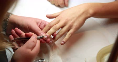 nehet : Nail technician removing cuticles from customers nails at the nail salon