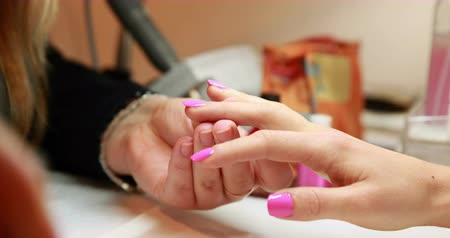 nehet : Nail technician painting top coat onto customers pink nails at the nail salon Dostupné videozáznamy