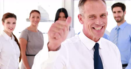 boss : Business team smiling at the camera with boss showing thumbs up in the office