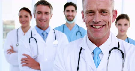 confiança : Doctor smiling at camera with team behind him at the hospital