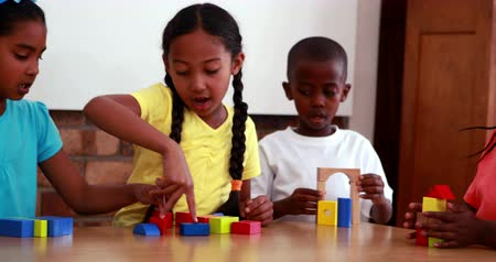bloklar : Pupils playing with building blocks in classroom in elementary school Stok Video