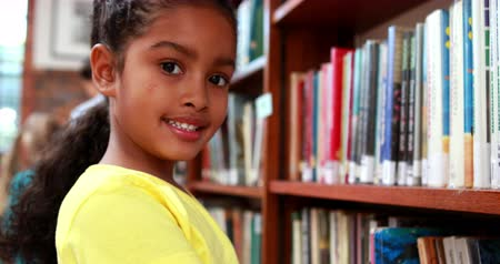 könyvtár : Little girl smiling at camera in the library in elementary school