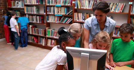 könyvtár : Pupils looking at the computer in library with their teacher in elementary school
