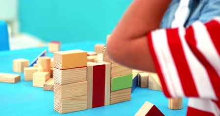 wood : Cute little boys playing with building blocks at table in playschool Stock Footage