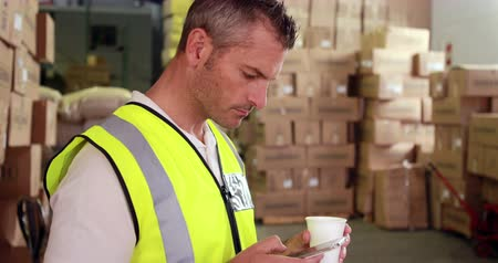 работник физического труда : Warehouse worker sending a text on his break in a warehouse