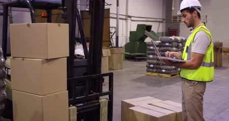 перевозка груза : Warehouse worker checking cardboard boxes for shipping in a warehouse