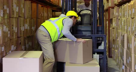 работник физического труда : Warehouse worker packing boxes on forklift in a large warehouse