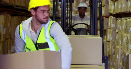 munkás : Warehouse worker packing boxes on forklift in a large warehouse