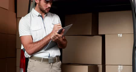 teslim : Delivery driver checking his list in a large warehouse