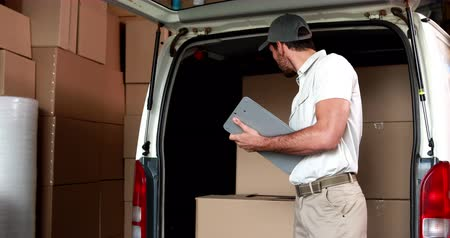 kurier : Delivery driver checking his list in a large warehouse