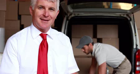 gerente : Delivery driver packing his van with manager smiling at camera in a large warehouse