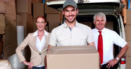 доставка : Delivery driver and business team smiling at camera in a large warehouse Стоковые видеозаписи
