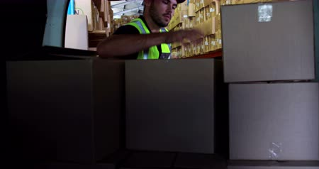 kurier : Delivery driver loading his van with boxes in a large warehouse Wideo