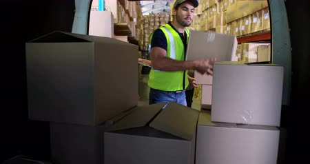 paket : Delivery driver loading his van with boxes in a large warehouse Stok Video