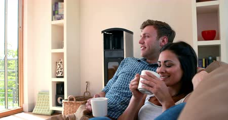 kipiheni magát : Cute young couple relaxing on the couch with coffee at home in the living room