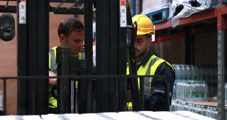 máquina : Warehouse worker talking with forklift driver in 4k video format