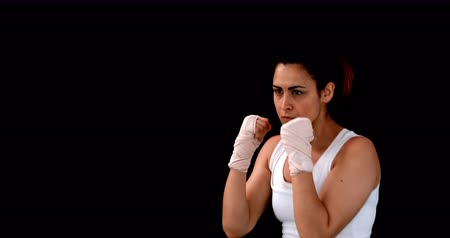puncs : Fit brunette punching with bandaged fists on black background in 4k format Stock mozgókép