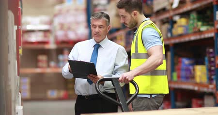 discussão : Warehouse worker talking with his manager in 4k video format Stock Footage