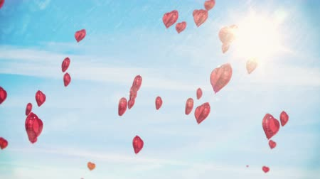 плавающий : Digital animation of Red hearts floating against blue sky