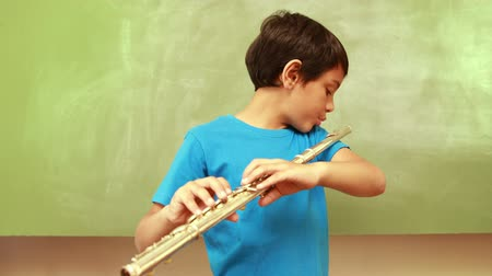 flet : Cute pupil playing flute in classroom at the elementary school Wideo
