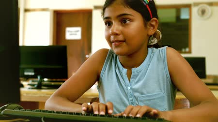 fare : Cute little pupil looking at laptop in classroom in slow motion