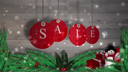 kardan adam : Digital animation of Red sale tags hanging against wood with festive decorations Stok Video