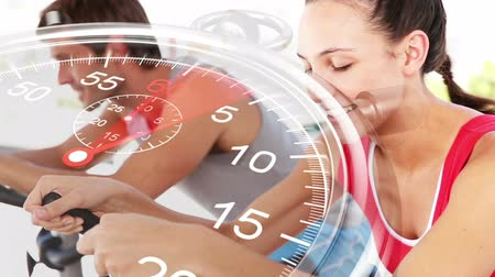 cycle : Digital animation of Stopwatch graphic over couple using exercise bikes