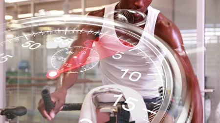 cycle : Digital animation of Stopwatch graphic over man using exercise bike Stock Footage
