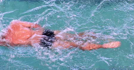 pływak : Fit swimmer doing the front stroke in the swimming pool in the leisure center