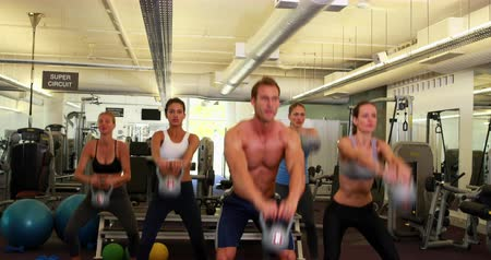 sınıf : Muscular instructor leading kettlebell class at the gym