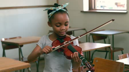anaokulu : Cute pupil playing violin in classroom in slow motion