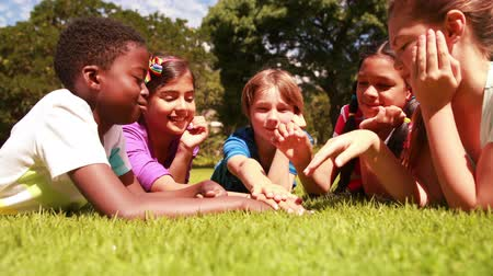 razem : Cute pupils lying on the grass with hands together outside on the garden