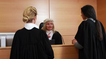 zęby : Judge looking at the witness swearing on bible in court room Wideo