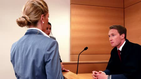 spravedlnost : Serious judge speaking with two lawyers in court room