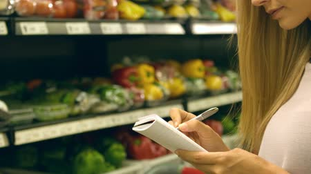 grocery : Woman checking her list while grocery shopping in slow motion