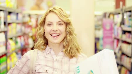 grocery : Young happy woman smiling at camera with thumbs up  Stock Footage