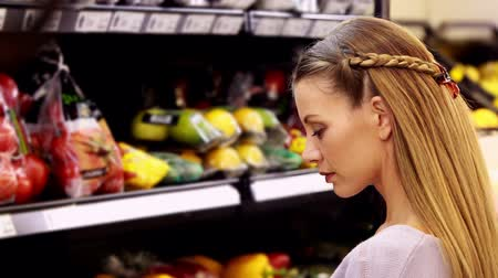 grocery : Young smiling woman looking at vegetables  Stock Footage