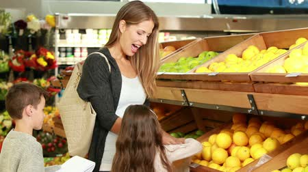 grocery : Mother and children picking out fruit in supermarket