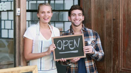 hipster : Waitress and hipster man holding open signboard at frontage of a cafe Stock Footage