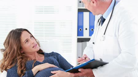 maternity hospital : Doctor talking to a smiling pregnant woman in the hospital Stock Footage