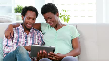 dialog : Cute couple looking at ultrasound scan on a tablet on the sofa Wideo